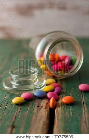 Spilled Chocolate Smarties Around Glass Jar