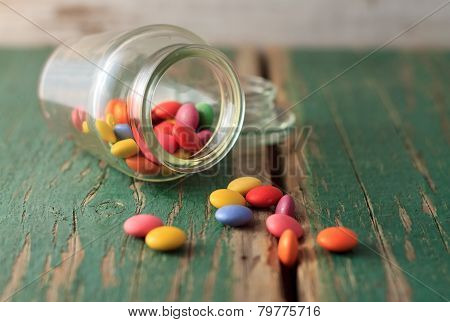 Spilled Chocolate Smarties On Green Wooden Board