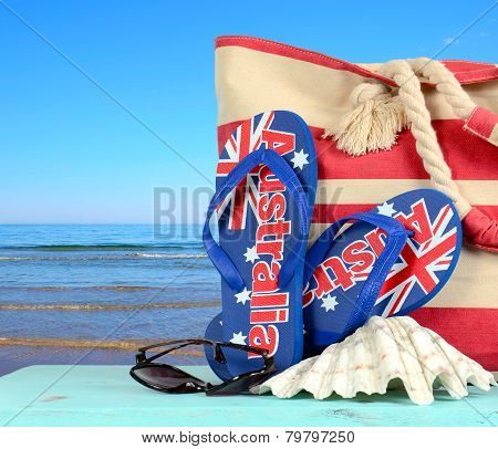 Australian Beach Scene With Aussie Sandals, Beach Bag, Sunglasses And Shell With View Of Blue Ocean.