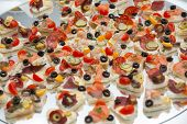 Different types of canapes on buffet table poster