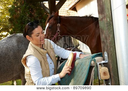 Young woman cleaning horse saddlery outdoors, brushing saddle-cloth.
