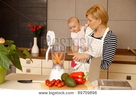 Young mother holding baby girl in arms, preparing food together in kitchen.