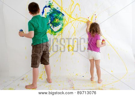 Two Young Children Freehand Painting On A Wall