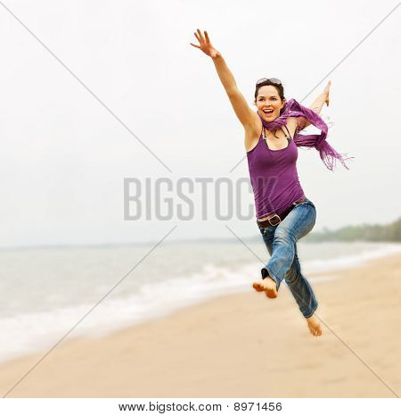 Beautiful Young Woman Taking A Great Leap On The Beach