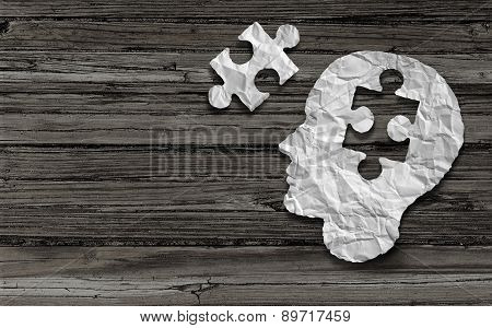 Mental health symbol Puzzle and head brain concept as a human face profile made from crumpled white paper with a jigsaw piece cut out on a rustic old double page spread horizontal wood background. poster