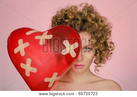 Upset Young Woman With Ball In Shape Of Heart