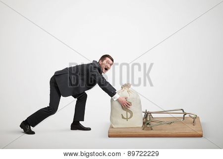 amazed man in formal wear reaching his hands to take bag with money in big mousetrap over light grey background
