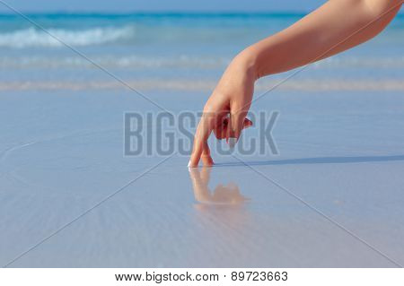 Female hand playing in the water on the beach