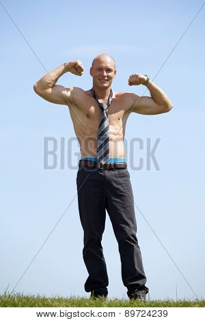Portrait of shirtless bald young man wearing tie holds his arms up in park