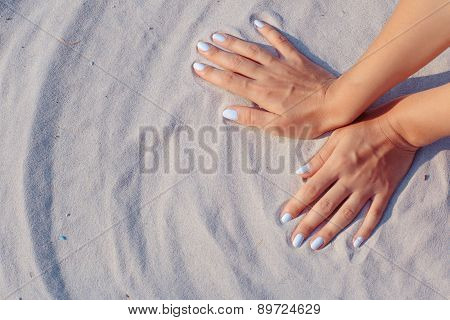 Female hands playing in sand