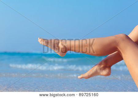 Female legs on sea background back lit