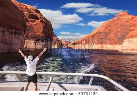 Man in  white shirt on the stern boat fascinated by nature. Artificial lake Powell on the Colorado River, USA. The lake is surrounded by picturesque beaches of the orange sandstone