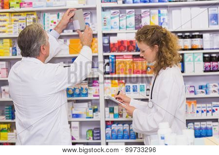 Pharmacists searching medicines with prescription at hospital pharmacy