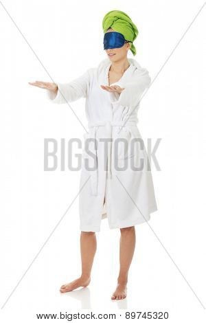 Sleepwalking woman in bathrobe and sleep mask