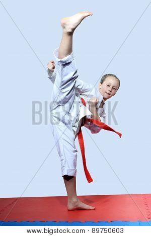 With a red belt sportswoman beats roundhouse kick leg