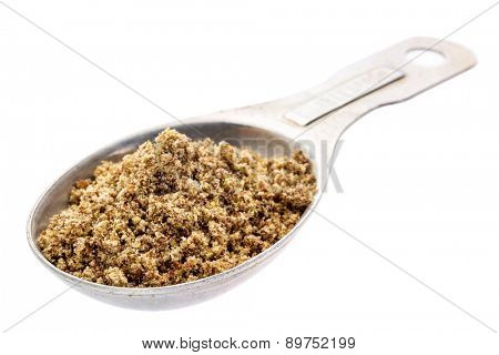 gluten free brown flax meal on a measuring aluminum tablespoon isolated with clipping paths