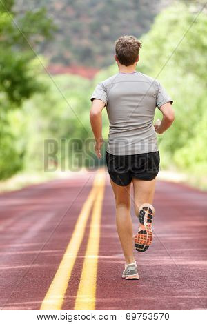 Running man runner working out for fitness. Male athlete on jogging run wearing sports running shoes and shorts working out for marathon. Full body length view showing back running away.