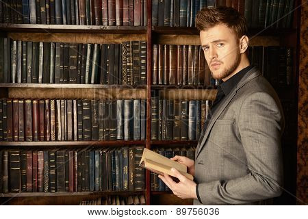 Handsome well-dressed man stands by bookshelves in a room with classic interior. Fashion.