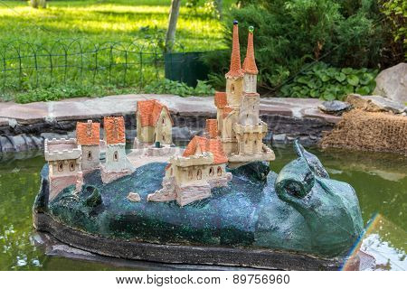 Garden Statue Of A Snail With Castle On Its Back In Pond