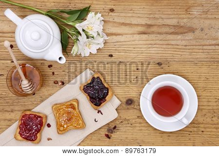 breakfast table with tea, teapot, cup of tea,  jam, bread and honey