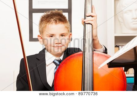 Smiling boy holding fiddlestick, play violoncello