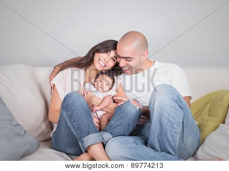 Portrait of happy cheerful family sitting on the couch at home, young parents enjoying time spent with their adorable newborn daughter