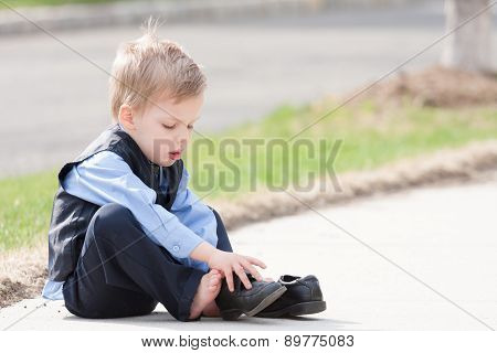 adorable toddler boy trying to put his shoes on