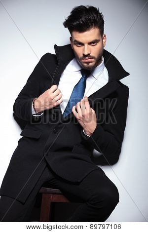 Young business man sitting on a chair while fixing his collar.