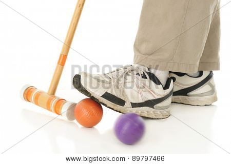 Close-up image of a croquet mallet hitting an orange ball under a player's foot to send off an opponent's purple ball.  Motion blur on mallet and purple ball.  On a white background.