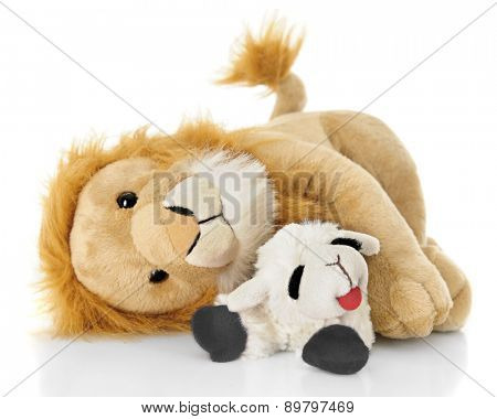 A toy lamb and lion peacefully laying down together.  On a white background.