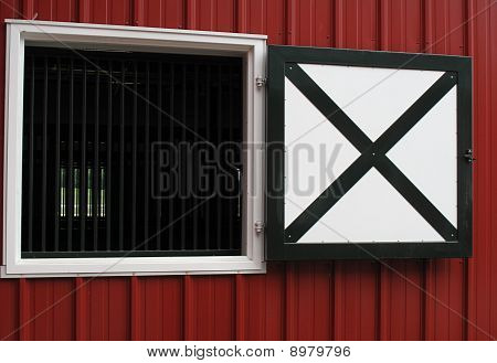red horse barn window framed in white with bars and black and white shutters. poster