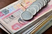 many one dirham coins placed on stack of hundred dirham notes. Close up. poster