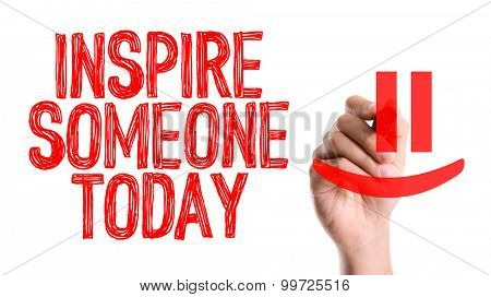 Hand with marker writing the word Inspire Someone Today