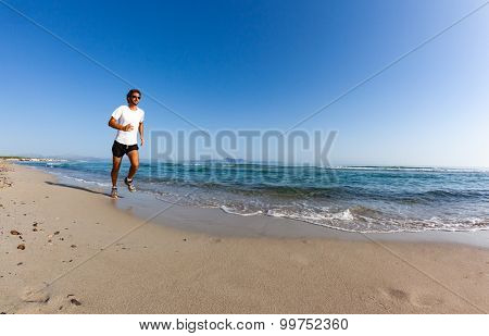 Man running on a sandy beach in a sunny day. Caucasian male, white shirt, summer season, spanish mediterranean coast. Large copy-space in the sky.