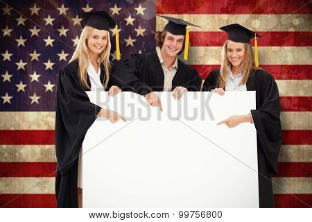 Three students in graduate robe holding and pointing a blank sign against usa flag in grunge effect
