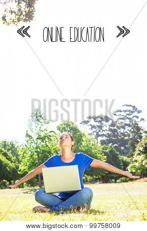 The word online education against carefree woman using laptop in park
