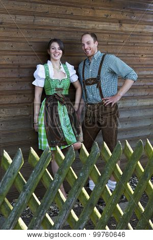Bavarian Couple Standing Behind A Wooden Fence