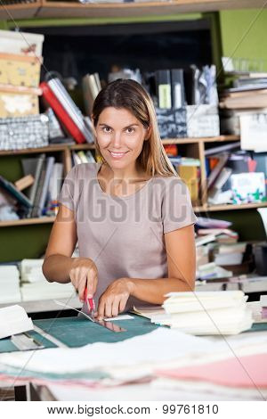 Portrait of mid adult female worker cutting paper in factory