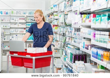 Smiling female chemist using laptop on medicine basket in pharmacy