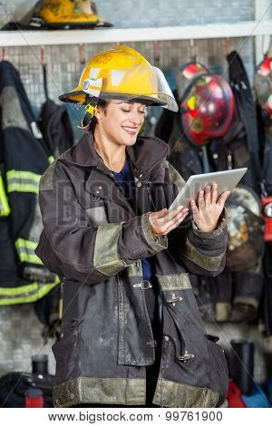Happy firewoman in uniform using digital tablet at fire station