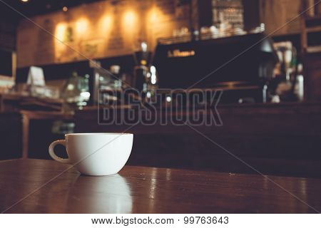 Vintage Tone Of White Cup Of Coffee On Wooden Bar In Coffee Shop Blur Background