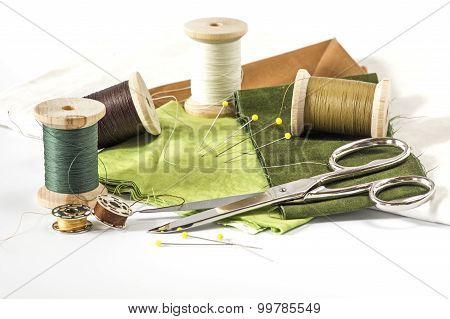 Scissors, fabrics and threads in green and brown