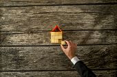 Overhead view of real estate or insurance agent constructing a house from a wooden cubes placing the last piece to finish the project on rustic desk in a conceptual image for house sale and security. poster