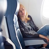 Tired blonde casual caucasian lady napping on uncomfortable seat while traveling by airplane. Commercial transportation by planes. poster