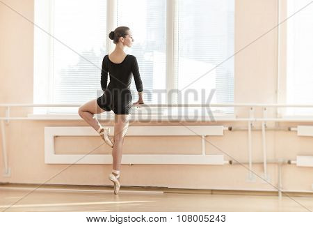 Young ballerina standing on poite at barre in ballet class.