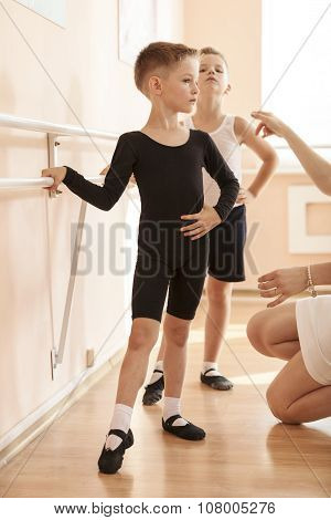 Young boys working at the barre in a ballet dance class.