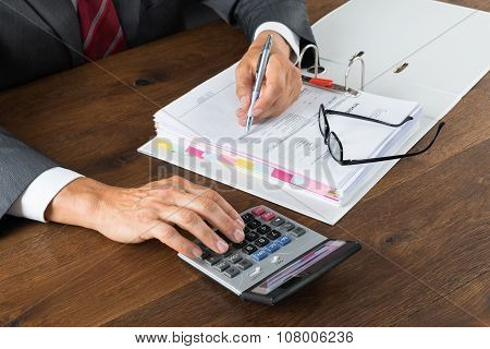 Midsection of accountant checking invoice with calculator at desk against gray background poster