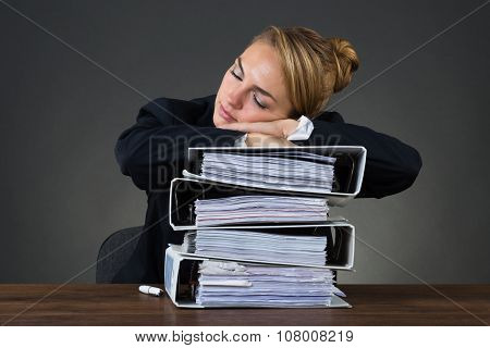 Tired businesswoman sleeping on stacked binders over black background poster