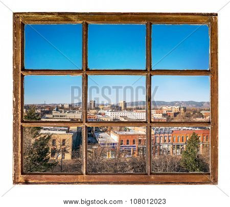 abstract cityscape view through a vintage sash window featuring the downtown of Fort Collins, Colorado with Rocky Mountains in a distant background