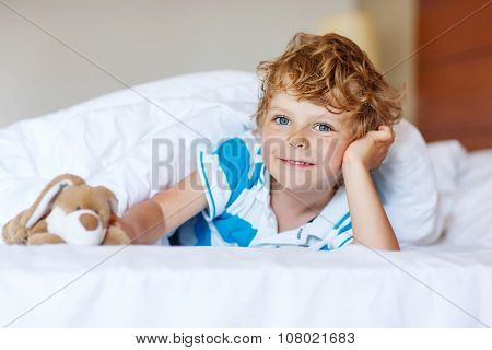 Adorable Kid Boy After Sleeping In His White Bed With Toy